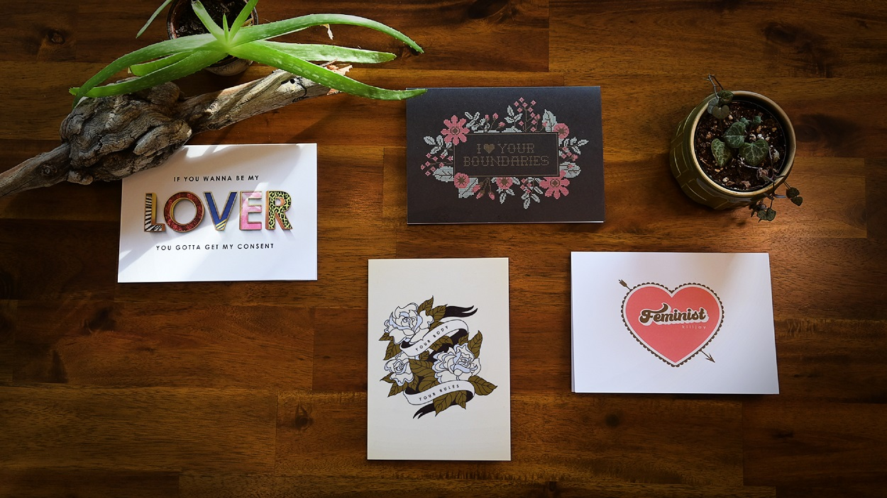 Four SACE Consent Greeting Cards Displayed On A Dark Brown Wood Table With Plants.