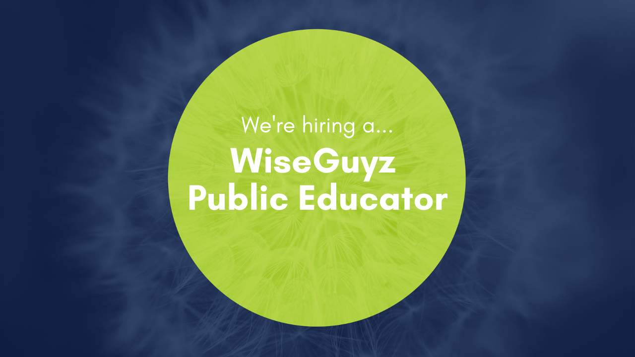 "Navy blue banner with a lime green circle in the centre with text that reads ""We're hiring a WiseGuyz public educator"""